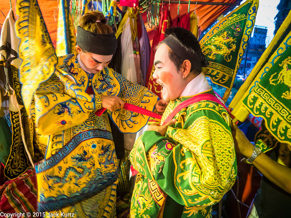 """14 MAY 2015 - BANGKOK, THAILAND:  Chinese opera performers put on their costumes before a show at the Pek Leng Keng Mangkorn Khiew Shrine in the Khlong Toey slum in Bangkok. Chinese opera was once very popular in Thailand, where it is called """"Ngiew."""" It is usually performed in the Teochew language. Millions of Chinese emigrated to Thailand (then Siam) in the 18th and 19th centuries and brought their culture with them. Recently the popularity of ngiew has faded as people turn to performances of opera on DVD or movies. There are still as many 30 Chinese opera troupes left in Bangkok and its environs. They are especially busy during Chinese New Year and Chinese holiday when they travel from Chinese temple to Chinese temple performing on stages they put up in streets near the temple, sometimes sleeping on hammocks they sling under their stage. Most of the Chinese operas from Bangkok travel to Malaysia for Ghost Month, leaving just a few to perform in Bangkok.      PHOTO BY JACK KURTZ"""