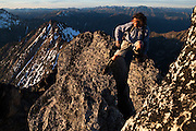 Kevin Steffa balances on the narrow summit block of Golden Horn at sunset in Okanogan National Forest, Washington.
