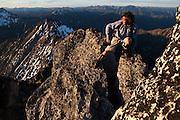 Kevin Steffa balances on the narrow summit block of Golden Horn at sunset in Okanogan National Forest, Washington.