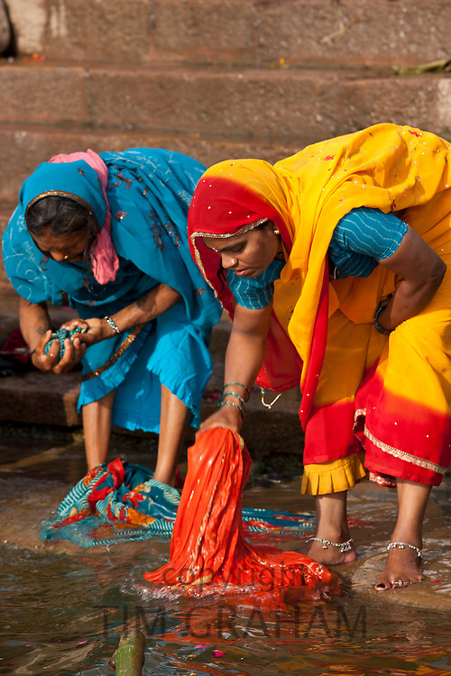 Indian Hindu pilgrims washing clothes and bathing in The Ganges River at Dashashwamedh Ghat in Holy City of Varanasi, India