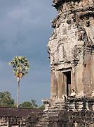 A local man sits by an entrance way to Angkor Wat, Angkor, Siem Reap Province, Cambodia