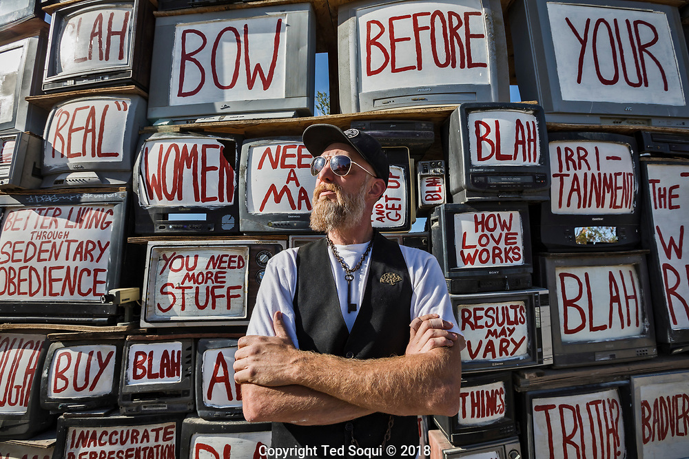 "Flip Cassidy painting his large ""Television Will Not Be Revolutionized"" art piece.<br /> East Jesus, a privately owned artist colony and sculpture garden located inside Slab City.<br /> Slab City and the local environs."