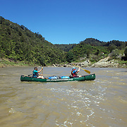 Kayaking on the Whanganui National Park, North Island..This park encloses the wild upper and middle reaches of the Whanganui River, which is New Zealand's longest navigable waterway. Beginning beneath the shadow of the central plateau's giant volcanoes, the 329 kilometre river winds its way to the Tasman Sea through an endless procession of forested valleys and hills...The river was once an important transport route for Maori, and many defensive pa (forts) were constructed on headlands along its sinuous course. Early European settlers and traders also used the river for transport, guiding their shallow-draft boats through the long narrow gorges that today provide so much enjoyment for kayakers. The paddling adventure that begins in Taumarunui and finishes in Pipiriki is known as the 'Whanganui Journey'.with Coastal Kayakers. Whanganui National Park, North Island. New Zealand. 30th December 2010. Photo Tim Clayton.