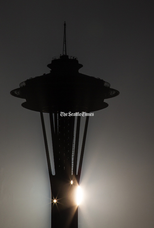 The sun peeks through the Space Needle as it sets at Lake Union Park. (Lindsey Wasson / The Seattle Times)