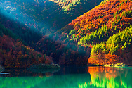 Spectacular lake by the autumn forest with green water