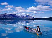 Fred Hirschmann paddling Grumman canoe on glassy water of Upper Twin Lake, Lake Clark National Park, Alaska.