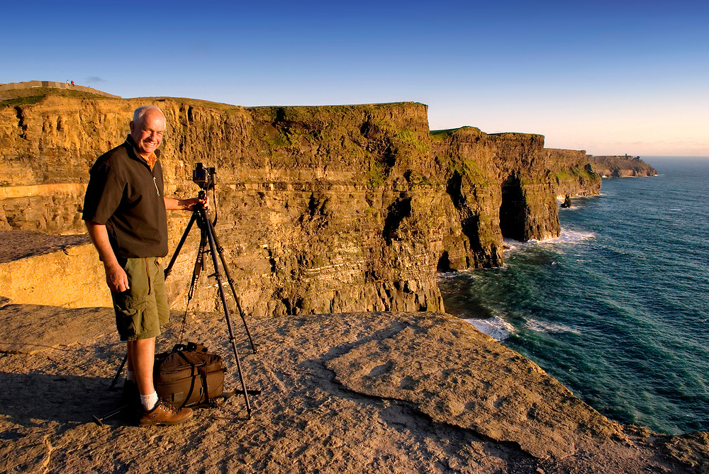 Photographer poses on the Cliffs of Moher; Clare Ireland Wild Atlantic Way
