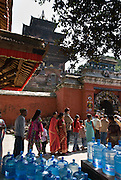 Behind the Lion Gate rises Taleju Temple. The three-roofed Taleju Temple was established in 1564, in a typical Newari architectural style and is elevated on platforms that form a pyramid-like structure. In the foreground, Hindu people line up to visit certain Durbar Square palace buildings which are only opened during Dasain Festival (or Durga Puja), which is Nepal's biggest annual festival, a 15-day family affair in Kathmandu Valley. Durga Puja celebrates the victory of the bloodthirsty goddess Durga over the forces of evil personified in the buffalo demon Mahisasura. Blue water bottles are lined up to serve thirsty festival crowds.