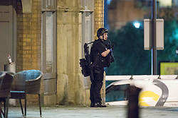 © Licensed to London News Pictures. 22/05/2017. Manchester, UK. Armed police search and clear Cathedral Gardens ahead of carrying out a controlled explosion . Police and other emergency services are seen near the Manchester Arena after reports of an explosion. Police have confirmed they are responding to an incident during an Ariana Grande concert at the venue. Photo credit: Joel Goodman/LNP