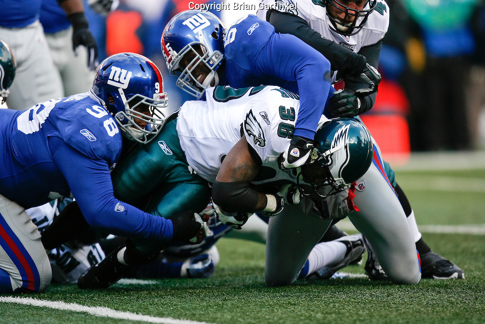 11 Jan 2009: Philadelphia Eagles running back Brian Westbrook #36 is tackled by New York Giants defensive tackle Fred Robbins #98 and linebacker Danny Clark #55 during the game against the New York Giants on January 11th, 2009.  The  Eagles won 23-11 at Giants Stadium in East Rutherford, New Jersey.