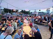 Nederland, The Netherlands, 23-7-2015 Recreatie, ontspanning, cultuur, dans, theater en muziek in de binnenstad. Hapjes eten bij ondergaande zon op de smkmrkt, smaakmarkt, aan de waalkade.  Foodfestival. Een van de tientallen feestlocaties in de stad. Onlosmakelijk met de vierdaagse, 4daagse, zijn in Nijmegen de vierdaagse feesten, de zomerfeesten. Talrijke podia staat een keur aan artiesten, voor elk wat wils. Een week lang elke avond komen ruim honderdduizend bezoekers naar de stad. De politie heeft inmiddels grote ervaring met het spreiden van de mensen, het zgn. crowd control. De vierdaagsefeesten zijn het grootste evenement van Nederland en verbonden met de wandelvierdaagse. Foto: Flip Franssen/Hollandse Hoogte