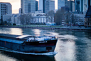 "Germany banned gatherings of more than 2 people called ""social distancing"" because of the coronavirus. A cargo ship is passing the city of Frankfurt on the river Main."