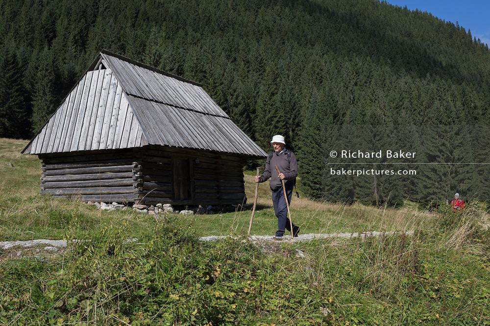 With the help of sticks, a walker makes his way past a mountain hut alongside the stony road in Dolina Chocholowska, a hiking route in the Polish Tatra mountains, on 17th September 2019, near Zakopane, Malopolska, Poland.