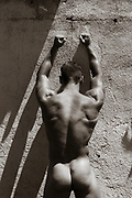 nude man against an adobe wall in New Mexico