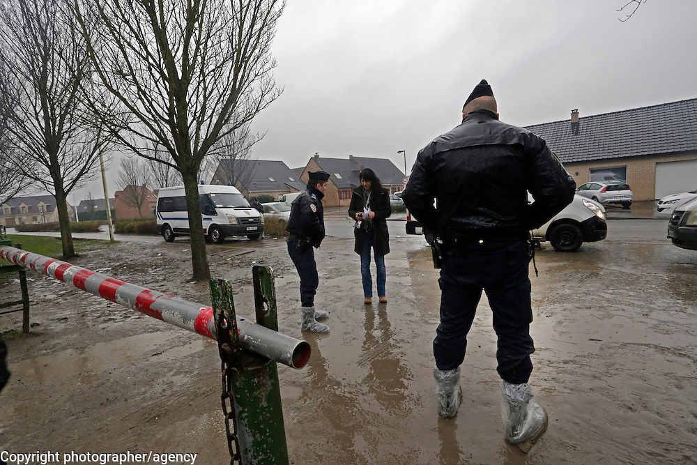French police guard the entrance to the plot of  land  in Grande-Synthe, near Dunkirk, that has become a de-facto refugee camp. A sign advertising the real estate as a development opportunity for an eco-village can be seen in the background.