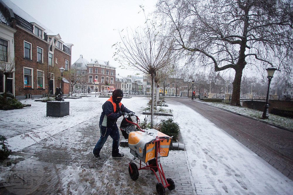In Utrecht loopt een postbesteller dikt ingepakt zijn ronde door de sneeuw.<br /> <br /> In Utrecht a postman is walking in the snow.