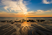 Sunsets directly offshore over the Andaman sea, Koh Lanta, Thailand. Gentle waves and an outgoing tide leave a fascinating pattern of miniature riverways like a giant epic landscape.