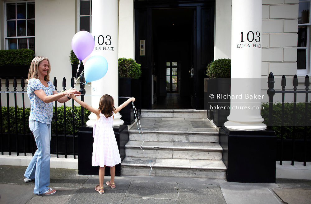 Young girl and mother tying birthday party balloons to railings of their immaculate house in Belgravia, London.