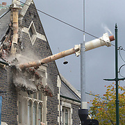 A damaged chimney is knocked down by demolition workers on an earthquake damaged building in Christchurch. A Powerful earth quake ripped through Christchurch, New Zealand on Tuesday lunch time killing at least 65 people as it brought down buildings, buckled roads and damaged houses, churches and the Cities Cathedral. 23rd February 2011.  Photo Tim Clayton