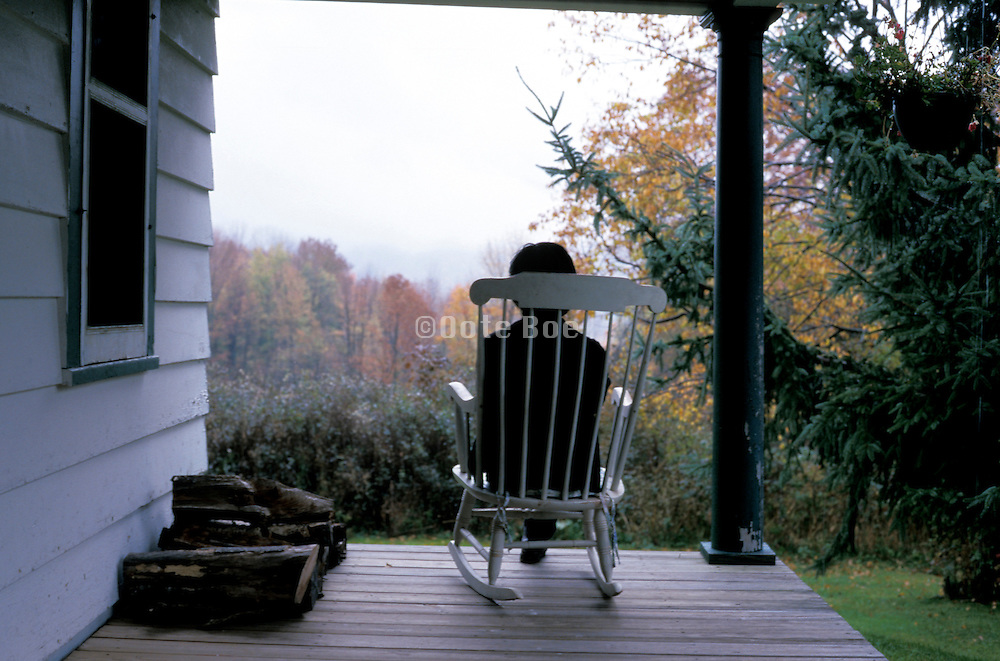 seated figure in rocking chair overlooking landscape