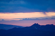 Rain falls over the ridges of the North Cascades, Washington, as the sunset illuminates the fog down in the valley.