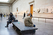 Two figures sitting in the British Museum, London, UK. Elgin Marbles horsemen from marble frieze on north side of Parthenon Athens 4th fourth century C BC.