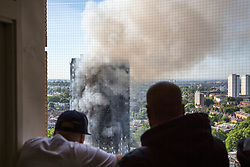 Residents look on as smoke billows from a fire that has engulfed the 24-storey Grenfell Tower in west London.