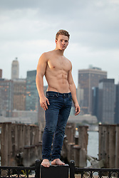 shirtless muscular man in jeans standing on a fence overlooking the New York Skyline