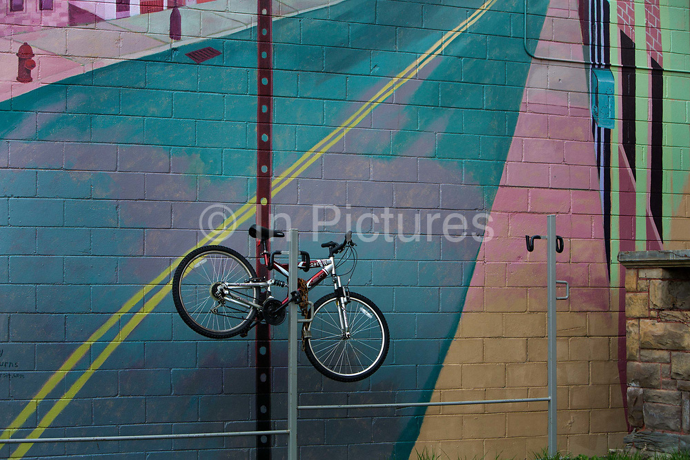 """Bike chained by a mural painted on cafe wall on Warren Avenue, near Waynne State University. Known as the world's traditional automotive center, """"Detroit"""" is a metonym for the American automobile industry and an important source of popular music legacies celebrated by the city's two familiar nicknames, the Motor City and Motown. Many neighborhoods remain distressed since the collapse of the motor industry. The state governor declared a financial emergency in March 2013, appointing an emergency manager. On July 18, 2013, Detroit filed the largest municipal bankruptcy case in U.S. history."""
