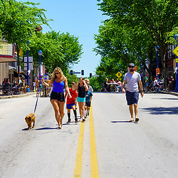 Phoenixville, PA, USA - June 14, 2020: Socially distanced, pedestrians walk in the middle of a closed street in the town.