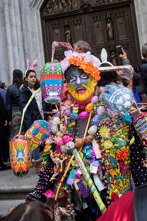 New York, NY, USA-27 March 2016. A man with a bizarre and colorful costume covered in decorative eggs, sculptural appendages, and assorted bits of color, on the steps of St. Patrick's Cathedral at the annual Easter Bonnet Parade and Festival.