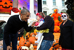 President Barack Obama hands treats out to local children and children of military families for trick-or-treat at the South Portico of the White House on Halloween, Oct. 31, 2014. (Official White House Photo by Pete Souza)<br /> <br /> This official White House photograph is being made available only for publication by news organizations and/or for personal use printing by the subject(s) of the photograph. The photograph may not be manipulated in any way and may not be used in commercial or political materials, advertisements, emails, products, promotions that in any way suggests approval or endorsement of the President, the First Family, or the White House.