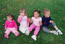 Multiracial group of children sitting together on grass in park,