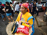 30 AUGUST 2016 - BANGKOK, THAILAND:  People leave the Poh Teck Tung Shrine with baskets full of food and clothing on the last day of Hungry Ghost Month in Bangkok. Chinese temples and shrines in the Thai capital host food distribution events during Hungry Ghost Month, during the 7th lunar month, which is usually August in the Gregorian calendar.         PHOTO BY JACK KURTZ