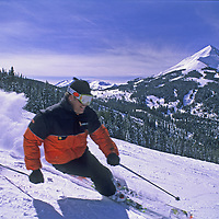 """SKIING, Big Sky, MT. Patrick Shanahan (MR) carves high speed turns on """"Africa"""" run.  Lone Mountain bkg."""