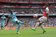 Diafra Sakho of West Ham United crosses the ball over Francis Coquelin of Arsenal. Barclays Premier League, Arsenal v West Ham Utd at the Emirates Stadium in London on Sunday 9th August 2015.<br /> pic by John Patrick Fletcher, Andrew Orchard sports photography.