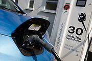 "Fast charging a Nissan Leaf electric car at an electrical charging point offering an EV 30 minute charge. The Nissan Leaf (Leading, Environmentally Friendly, Affordable, Family) is a five-door hatchback electric Nissan car. Its official range is 117 kilometres with an energy consumption of 765 kilojoules per kilometre and rated the Leaf's combined fuel economy at 2.4 L/100 km. The Leaf has a range of 175 km (109 mi) on the New European Driving Cycle. CHAdeMO is the trade name of a quick charging method for battery electric vehicles delivering up to 62.5 kW of high-voltage direct current via a special electrical connector. CHAdeMO is an abbreviation of ""CHArge de MOve"", equivalent to ""charge for moving"". The name is a pun for O cha demo ikaga desuka in Japanese, (or ""How about some tea?""), referring to the time it would take to charge a car."