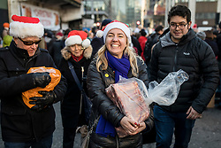 © Licensed to London News Pictures. 24/12/2018. London, UK. A happy customer carries away her purchase as butcher Harts of Smithfield auction off cuts of meat to the public on Christmas Eve at Smithfield Market in London. Photo credit: Rob Pinney/LNP