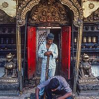 A Tibetan Buddhist man lights an offering fire   at Swaymbhu Temple in Kathmandu, Nepal, 1986.