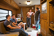 "Lukas, Liam, Simon and Robert, overseas seasonal workers from Ireland, England and Germany, in their trailer...Life of custom harvesters: custom harvesting or custom combining is the business of harvesting of crops for others. Custom harvesters usually own their own combines and work for the same farms every harvest season. Custom harvesting relieves farmers from having to invest capital in expensive equipment while at the same time maximizing the machinery's use. .Harvesters travel North to South through the US, living in trailers, following the season, usually hiring overseas seasonal workers in need of improving their harvesting experience on very large combines (harvesting machines)...A 4-weeks road trip across the USA, from New York to San Francisco, on the steps of Jack Kerouac's famous book ""On the Road"".  Focusing on nomadic America: people that live on the move across the US, out of ideology or for work reasons."