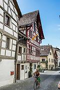 Bicyclist rides by Haus Vetter, on Bodenseeradweg in Stein am Rhein village, Schaffhausen Canton, Switzerland, Europe.