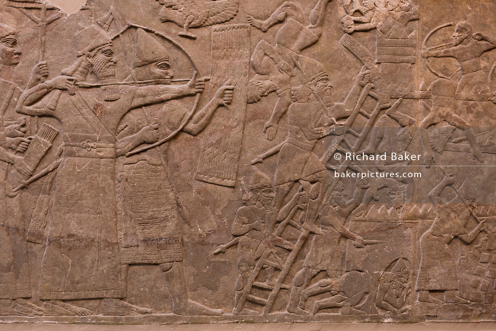 A detail from an ancient Assyrian stone carving (865-860BC)depicting an attack on an enemy town by a river, in the British Museum, on 11th April 2018, in London, England.