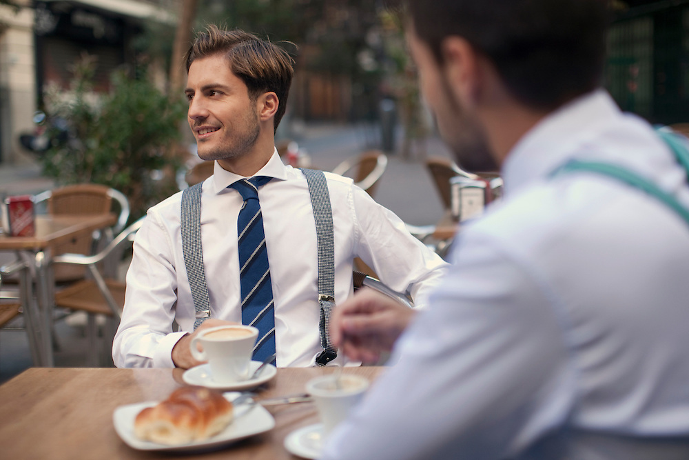 Young well-suited executives enjoy breakfast out in the street in Madrid, Spain.