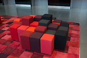 Red cube seating area in a modern office building, London, UK.