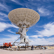 """The Karl G. Jansky Very Large Array (VLA) is one of the world's premier astronomical radio observatories. Visit the VLA on the Plains of San Agustin fifty miles west of Socorro, between the towns of Magdalena and Datil, in New Mexico, USA. US Route 60 passes through the scientific complex, which welcomes visitors. The VLA is a set of 27 movable radio antennas on tracks in a Y-shape. Each antenna is 25 meters (82 feet) in diameter. The data from the antennas is combined electronically to give the resolution of an antenna 36km (22 miles) across, with the sensitivity of a dish 130 meters (422 feet) in diameter. After being built 1973-1980, the VLA's electronics and software were significantly upgraded from 2001-2012 by at least an order of magnitude in both sensitivity and radio-frequency coverage. The VLA is a component of the National Radio Astronomy Observatory (NRAO). Astronomers using the VLA have made key observations of black holes and protoplanetary disks around young stars, discovered magnetic filaments and traced complex gas motions at the Milky Way's center, probed the Universe's cosmological parameters, and provided new knowledge about interstellar radio emission. The VLA was prominently featured in the 1997 film """"Contact,"""" a classic science fiction drama film adapted from the Carl Sagan novel, with Jodie Foster portraying the film's protagonist, Dr. Eleanor """"Ellie"""" Arroway, a SETI scientist who finds strong evidence of extraterrestrial life. This panorama was stitched from 3 overlapping photos."""
