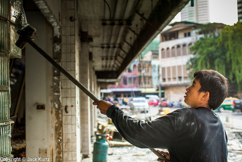 """13 DECEMBER 2012 - BANGKOK, THAILAND:   A worker knocks out glass blocks in a corner office at """"Washington Square"""" a notorious entertainment district off Sukhumvit Soi 22 in Bangkok. Demolition workers on many projects in Thailand live on their job site tearing down the building and recycling what can recycled as they do so until the site is no longer inhabitable. They sleep on the floors in the buildings or sometimes in tents, cooking on gas or charcoal stoves working from morning till dark. Sometimes families live and work together, other times just men. Washington Square was one of Bangkok's oldest red light districts. It was closed early 2012 and is being torn down to make way for redevelopment.    PHOTO BY JACK KURTZ"""