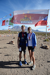 © Licensed to London News Pictures. 14/11/2013.<br /> <br /> British teenager Connor Brown, bib no. 5 & mum Yvonne Brown.<br /> <br /> Inaugural Volcano Marathon, Atacama Desert, Chile. The race took place in the Atacama Desert in Chile, beginning at an altitude of 4,400 metres (14,500 feet) in the vicinity of Lascar Volcano. It was a gruelling affair for many of the competitors who had to encounter some challenging hills and manage the impact of the heat and oxygen deprivation. The average altitude of the entire race was close to 4,000 metres and temperatures reached the mid 20s Celsius, or almost 80 Degrees Farenheit.<br /> <br /> Photo credit : Mike King/LNP<br /> <br /> Further information and link to video here: https://www.dropbox.com/s/0277bepxvo0t8il/Marathon%20copy.txt
