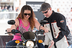 "Christina Lazar of Sunrise, FL with Harley-Davidson's Jim Edens in the ""Jumpstart"" display of the Harley-Davidson area at Daytona International Speedway during the Daytona Bike Week 75th Anniversary event. FL, USA. Saturday March 5, 2016.  Photography ©2016 Michael Lichter."