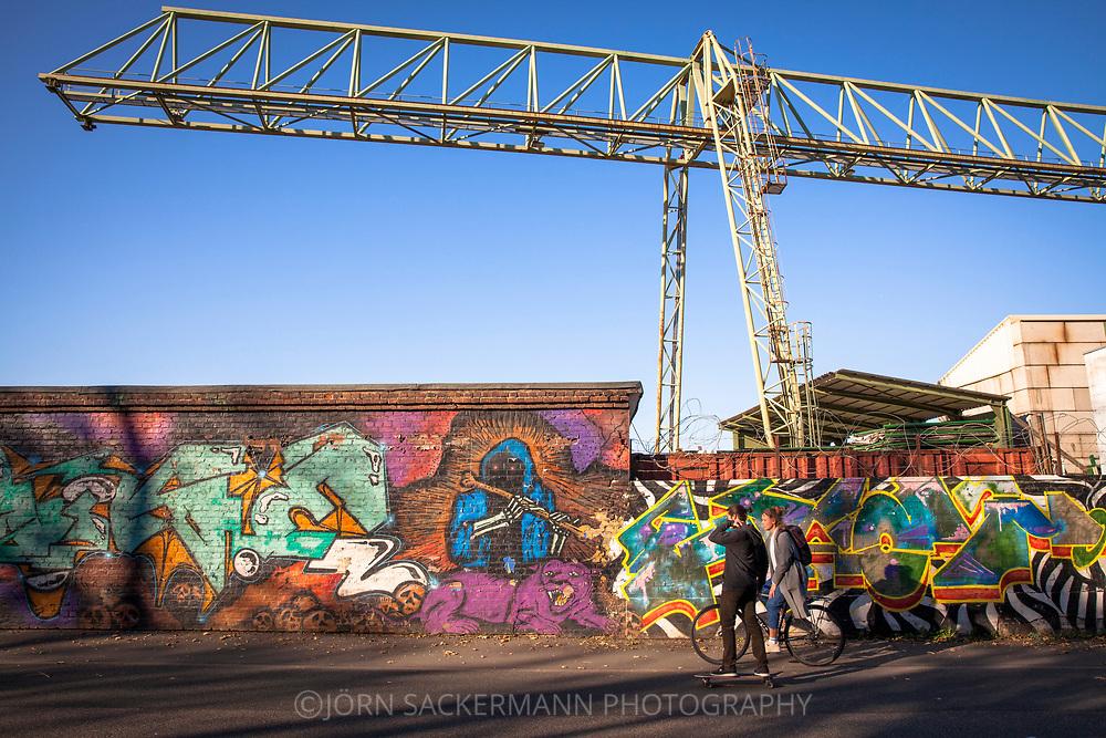 crane and wall with graffiti in the port  Deutz, Cologne, Germany.<br /> <br /> Verladekran und Mauer mit Graffitis im Deutzer Hafen, Koeln, Deutschland.