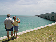 Couple taking a picture of the 7 Miles bridge from and to Key West USA Route 1